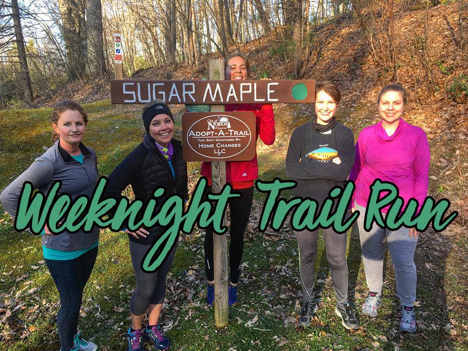 Photo of trail runners beside trail sign